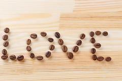 Inskriftförälskelse med kaffebönor Arkivfoton