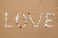Inskriftförälskelse som göras från skal på sand Royaltyfri Fotografi