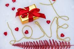 Inskriftförälskelsen av en guld- kedja på snön två röda hjärtor ligger på en ask med en röd bandpilbåge på valentins dag A royaltyfria foton