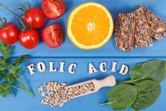 Inskriftfolsyra med sund näringsrik mat som källmineraler, vitaminet B9 och diet-fiber royaltyfri foto