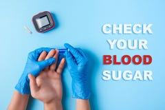 Inskriftkontroll ditt blodsocker, sjuksköterska som gör ett blodprov med lansetten Hand för man` s, röd bloddroppe och glukosmete arkivbild