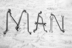 InskriftMANNEN är skriftlig vid arbetshjälpmedel Ordet MAN utgöras av hjälpmedel för ett arbete Royaltyfri Foto
