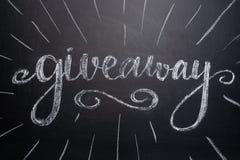 Inskriftpresentartikeln är skriftlig på en svart tavla med gåvor Fördelning av gåvor Blogg bloggers, sociala nätverk, instagram fotografering för bildbyråer