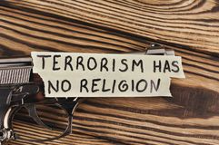 InskriftTERRORISM HAR INGEN RELIGION på sönderrivet papper och den glansiga pistolen royaltyfria bilder