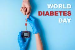 Inskriftvärldssockersjuka dag, sjuksköterska som gör en hand för ` s för man för blodprov med rött blod att tappa och glukosmeter arkivbild