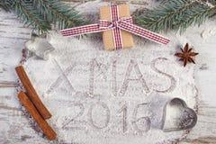 Inskrypci xmas 2016 pisać na mące na cieście dla miodownika, prezenta i świerczyny gałąź, Fotografia Stock