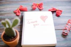 Inskrypcja kocham ciebie na białym notepad na drewnianym tle obrazy royalty free