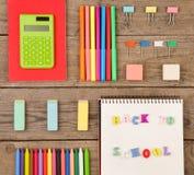 inskrypcja & x22; popiera school& x22; , kalkulator, notepads, markiery i inny materiały na brown drewnianym stole, fotografia stock