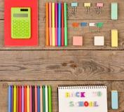 inskrypcja & x22; popiera school& x22; , kalkulator, notepads, markiery i inny materiały na brown drewnianym stole, zdjęcie royalty free