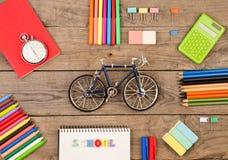inskrypcja & x22; school& x22; , bicyklu model, stopwatch, kalkulator, notepads i inny materiały na brown drewnianym stole, Obraz Royalty Free