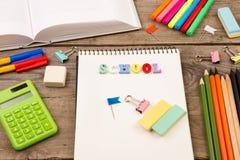 inskrypcja & x22; school& x22; , książka, kalkulator, notepad i inny materiały na brown drewnianym stole, Obraz Stock