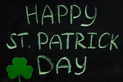 Inskrypcja z zieleni kredą na chalkboard: Szczęśliwy St Patrick dzień koniczyna liść obraz stock