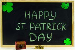 Inskrypcja z zieleni kredą na chalkboard: Szczęśliwy St Patrick dzień koniczyna liść Klatka piersiowa z monetami obrazy royalty free