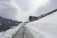 Insnöad kabin på en schweizisk bergssida arkivfoton