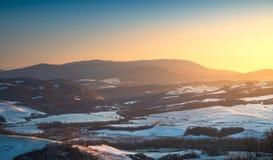 Insnöade Tuscany Vinterpanoramasikt på solnedgången italy siena royaltyfri bild