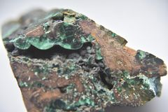 The edge of Green malachite in the natural condition. Insolations of green malachite in the medium of coper stock photography