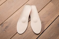 Orthopedic insoles on wooden boards. Insoles for flatfoot. insoles close up. medical insoles. orthopedic purpose insoles. insoles for problem feet stock images
