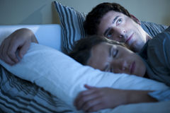 Insomnia. Image of a couple in bed, man cannot sleep Stock Photo
