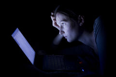 Insomnia. Young woman with laptop at night Stock Photography