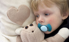Insomnia. Tired child with teddy bear and pacifier next to a heart. Similar images: 9274468 and 9227165 Royalty Free Stock Photo