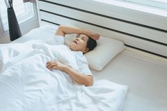 Insomnia in elderly asian woman on her bedroom,Female lying suffering from headache at house royalty free stock photo
