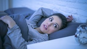 Insomnio sufridor hermoso joven de la mujer latina triste y preocupante y problema del desorden durmiente incapaz de dormir tarde imagen de archivo