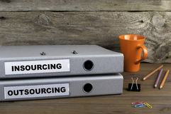 Insourcing and Outsourcing - two folders on wooden office desk Stock Photos