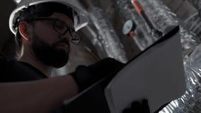 Inspeção do sistema de aquecimento da caldeira: o homem, vestindo no capacete faz a anotação filme