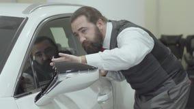 Inspecteert de portret aantrekkelijke leuke zekere gebaarde zakenman in een pak onlangs gekochte auto van de auto stock videobeelden