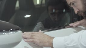 Inspecteert de portret aantrekkelijke zekere gebaarde mens in een pak onlangs gekochte auto van het autohandel drijven Auto stock videobeelden
