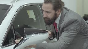 Inspecteert de portret leuke zekere gebaarde zakenman in een pak onlangs gekochte auto van het autohandel drijven stock videobeelden