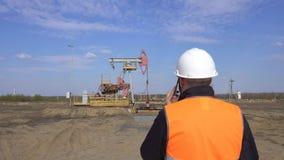 Inspecteur en chef masculin dans un gilet de signal parlant au téléphone sur le fond de pétrole de station de pompage, gaz et clips vidéos