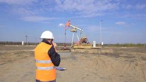Inspecteur en chef masculin dans un gilet de signal parlant au téléphone sur le fond de pétrole de station de pompage, gaz et banque de vidéos