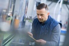 Inspecteur masculin mûr écrivant sur le presse-papiers dans l'usine photographie stock libre de droits