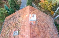 Inspectie van het rode betegelde dak van een ééngezinshuis, inspectie van de voorwaarde van de tegels op het dak van losgemaakt stock fotografie