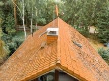 Inspectie van het rode betegelde dak van een losgemaakt huis, met een behandelde schoorsteen en een satellietantenne stock foto's