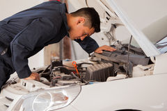 Inspecting a car engine. Young mechanic wearing an overall inspecting an engine at an auto shop Royalty Free Stock Images