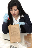 Inspecting evidence. A police detective inspecting and cataloging evidence Royalty Free Stock Images