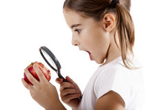 Inspecting microbes. Little girl with a magnifying glass inspecting microbes on a red apple Royalty Free Stock Photography