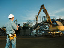 Inspecting recycling process. Back view of engineer wearing protective equipment, holding digital tablet and looking at scrap metal pile Stock Image
