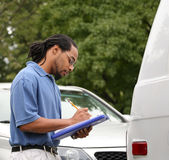 Inspecting Van Damage. An insurance agent or adjuster inspects and records damage to corner of work van Royalty Free Stock Images