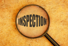 Inspection. Magnifying glass focusing on the word inspection stock photos