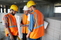 Inspection on Construction Site. Group of three workmen wearing protective helmets and vests standing among concrete walls on construction site discussing Royalty Free Stock Photography