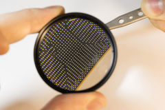 Inspection the contacts of a bga chip under a magnifying glass. Keep the chip tweezers Royalty Free Stock Photography