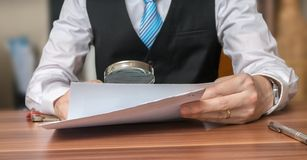 Inspection of document with magnifying glass. Layer is analysing contract.  stock image
