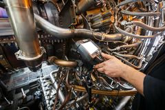 Inspection of a gas turbine engine using a Video Endoscope. Search for defects inside the turbine and shooting on video, photos. Using a measuring instrument stock photos