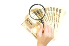 Inspection money yen japan with magnifying glass on white background.  Stock Photo