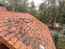 Inspection of the red tiled roof of a single-family house, inspection of the condition of the tiles on one roof side.  stock image