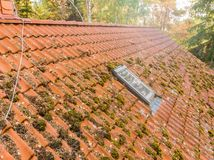 Inspection of the red tiled roof of a single-family house, inspection of the condition of the tiles on one roof side.  royalty free stock images