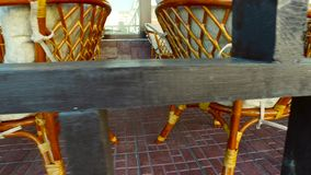 Inspection of the summer cafe. Evening summer city. Sunny. Inspection of the summer cafe. Verandah cafe filled with wooden wicker furniture. Worktops table made stock video
